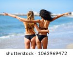 rear view of two young women... | Shutterstock . vector #1063969472
