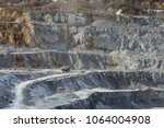 Large quarry dumper moving on the road in a limestone quarry against the background of a stepped terraced relief. Mining industry. Mine and quarry equipment.
