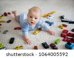 adorable baby boy  lying on the ... | Shutterstock . vector #1064005592