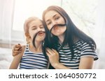 mom and her child daughter are... | Shutterstock . vector #1064050772