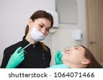 Small photo of Candid shot of positive professional female dentist wearing mask and gloves holding syringe, going to anesthetize tooth nerve of smiling woman patient before dental treatment. Anesthesia and numbing