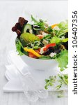 Healthy fresh gourmet raw green salad, lettuce tomato peppers and feta cheese with cutlery - stock photo