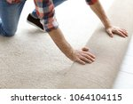 man rolling out new carpet... | Shutterstock . vector #1064104115