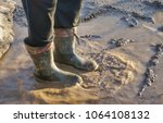 a man in large dirty rubber... | Shutterstock . vector #1064108132