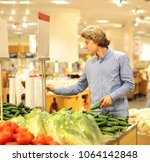 young man buying vegetables at... | Shutterstock . vector #1064142848