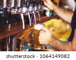 barman hand at beer tap pouring ... | Shutterstock . vector #1064149082