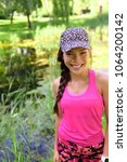 Small photo of Happy smiling young Asian girl in sportswear sports cap and pink activewear portrait. Chinese Caucasian multiracial runner woman in her 20s in outdoor city park active lifestyle.