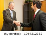 handshake between businessmen | Shutterstock . vector #1064212382
