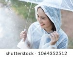 rainy day asian woman wearing a ...   Shutterstock . vector #1064352512