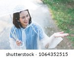 rainy day asian woman wearing a ... | Shutterstock . vector #1064352515
