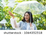 rainy day asian woman wearing a ... | Shutterstock . vector #1064352518