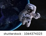 astronaut in outer space on... | Shutterstock . vector #1064374325
