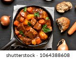 Small photo of Goulash, beef stew in cast iron pan, top view, close up