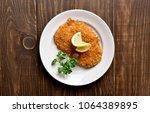 chicken schnitzel on plate over ... | Shutterstock . vector #1064389895