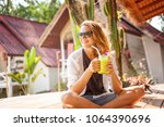 beautiful young woman sits in a ... | Shutterstock . vector #1064390696