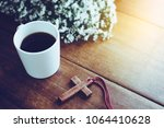 Small photo of the wooden cross and a cup of coss on wooden table with flower against 'window light, Christian background with copy space