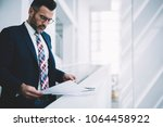 concentrated mature businessman ... | Shutterstock . vector #1064458922