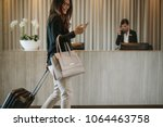 Stock photo woman using mobile phone and pulling her suitcase in a hotel lobby female business traveler 1064463758