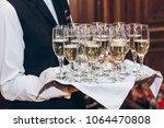 waiter serving stylish golden... | Shutterstock . vector #1064470808