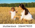 mom and daughter walking in the ... | Shutterstock . vector #1064479055