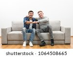 the two happy men on the sofa... | Shutterstock . vector #1064508665