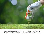 hand hold golf ball with tee on ... | Shutterstock . vector #1064539715