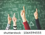 students raised up fingers... | Shutterstock . vector #1064594555