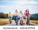 family riding their bicycles on ... | Shutterstock . vector #1064625998