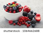 ripe and sweet berries in bowl... | Shutterstock . vector #1064662688