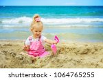 baby girl playing in the sand... | Shutterstock . vector #1064765255