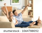 young couple watching tv on... | Shutterstock . vector #1064788052