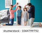 parents measuring height of... | Shutterstock . vector #1064799752