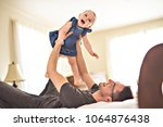 father playing with her baby in ... | Shutterstock . vector #1064876438