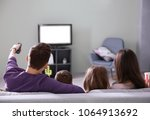 family watching tv on sofa at... | Shutterstock . vector #1064913692