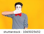 Small photo of Don't say anymore. Mime man closed mouth his hands
