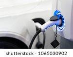 charging an electric car... | Shutterstock . vector #1065030902