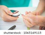 nurse's hands using glucometer... | Shutterstock . vector #1065169115