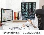 female doctor sitting at desk... | Shutterstock . vector #1065202466