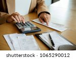woman with bills and calculator.... | Shutterstock . vector #1065290012