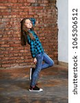 Small photo of Portrait full growth young hipster teenager girl on brick wall background.Youthful in bright blue shirt in cage posing for advertising youth clothing,store.Teenager raising hand up holding hair.