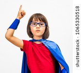 Small photo of clever fun super hero child with eyeglasses raising her smart finger for surprising idea, dynamic education and young critical mindset over white background