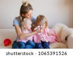 mother taking care of her sick... | Shutterstock . vector #1065391526