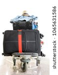 Small photo of A pile of luggage on a cart at the airport. Suitcase loaded on the trolley, stand in the hall.