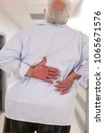 Small photo of Overweight man with acute back ache bending over backwards to attenuate the pain