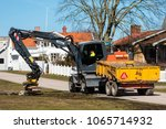 Small photo of Morbylanga, Sweden - April 6, 2018: Documentary of everyday life and environment. Atlas digger equipped with brush attachment brushing or vibrating the park lawn soil beside the road.