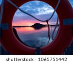 Small photo of Sunset in the harbor, little island seen through the lifebuoy, Sørenga, Oslo, Norway