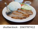 Small photo of Thai food named Kor Moo Yang - Selective focus on Roasted pork neck with rice, cucumber sliced, tomato sliced,salad, and spicy sauce on wood table.