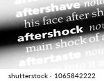 Small photo of aftershock word in a dictionary. aftershock concept.
