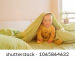 cute baby boy  playing in bed... | Shutterstock . vector #1065864632