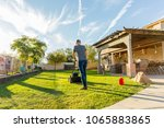man mowing back yard in the... | Shutterstock . vector #1065883865
